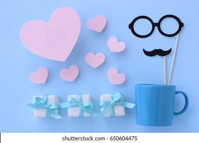 Small gift boxes with hearts. Mustaches and glasses in blue mug. Blue background.flat lay top view.