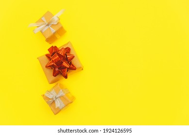 Small gift boxes on a yellow background.The boxes are festively packed. The concept of a holiday and gifts. Empty space for the text.
