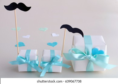 Small gift boxes with pale blue bow, hearts and mustaches. Happy father's day concept