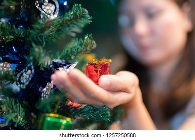 Small gift in the hands of a woman indoor. Shallow depth of field with focus on the little box.