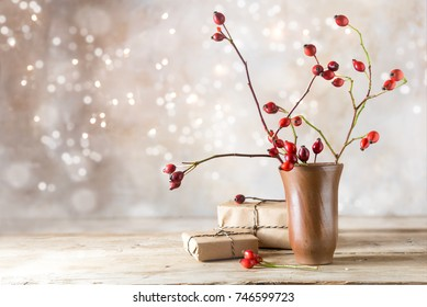 small gift parcels and rosehip branches on a rustic wooden table against a vintage wall with blurred bokeh lights, autumn or christmas decoration with copy space, selected focus