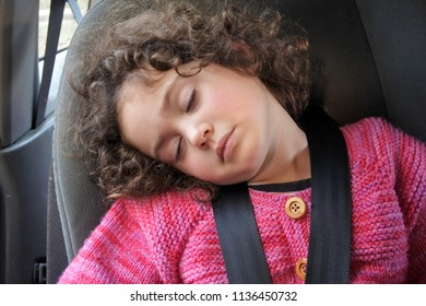 Small girl (age 03) sleeping in a car seat during a road trip.