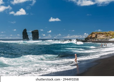 Small girl and blue waves on Mosteiros beach (praia Mosteiros), in the municipality of Ponta Delgada on the Portuguese island of Sao Miguel in the Azores.