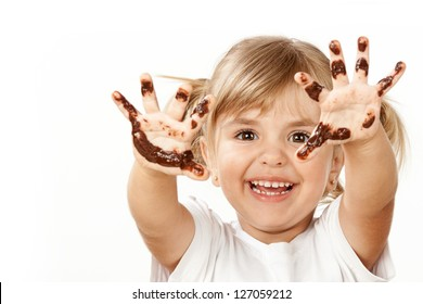 Small girl with chocolate smeared all over her face and fingers.