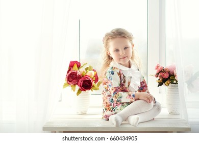 Small girl in colorful dress with flowers in hair. Facial expression.