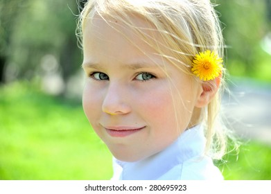 Small girl with dandelion behind her ear looking on camera