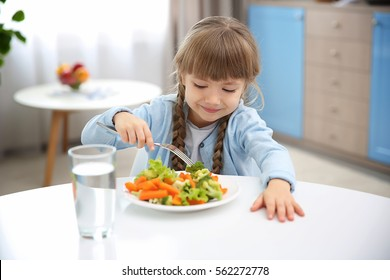 Small girl eating vegetables in kitchen