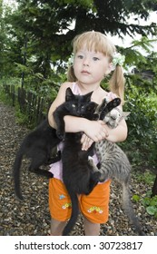 Small girl embraces by hands three kittens