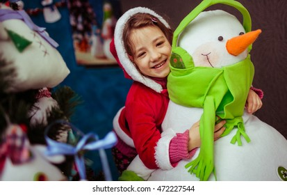 The small girl embracing her snowman
