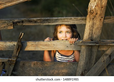 Small girl enjoy being behind an old wooden fence