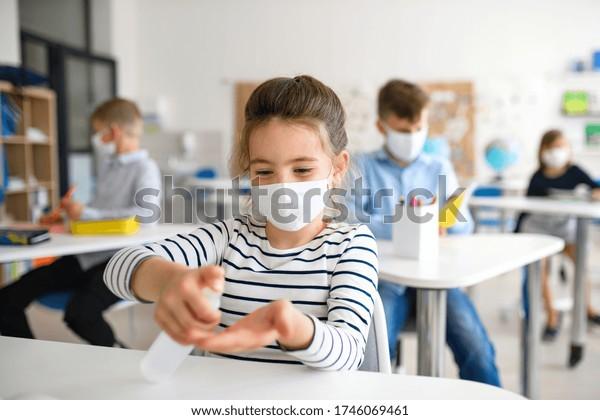Niña pequeña con mascarilla en la escuela después del bloqueo de covid-19, desinfectando las manos.