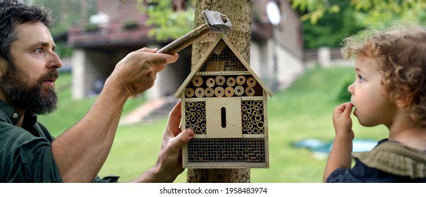 Small girl with father holding bug and insect hotel in garden, sustainable lifestyle.