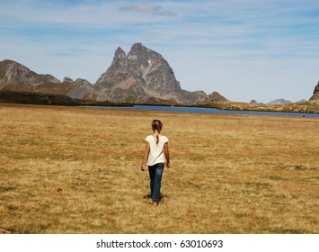 Small girl in focus, photografed from back, walking at Anayet plateau via the lake, Its Aragon, Spain. Beautyful peak du Midi d'Ossau in French site of Pytenees is at background