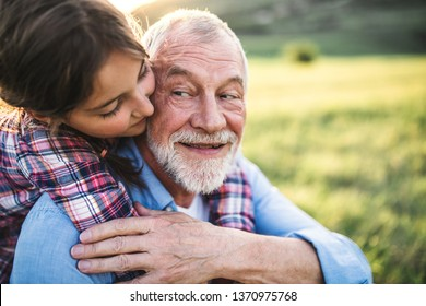 A small girl with grandfather outside in spring nature, having fun.