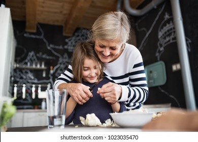 A small girl with grandmother cooking at home.