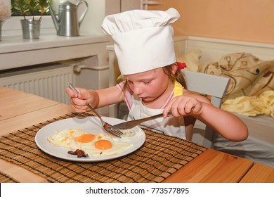 Small girl has a snack. Little girl eats ham and eggs. Cute girl wears chef costume.  Family and childhood concept