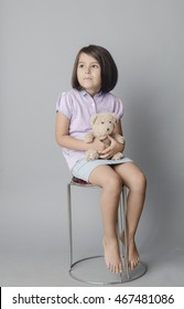 Small girl with her bear toy isolated inside studio