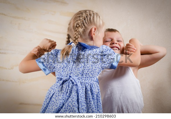Small girl with her blond hair in pigtails fighting with a young boy who is grimacing in anger as they wrestle together with their arms locked