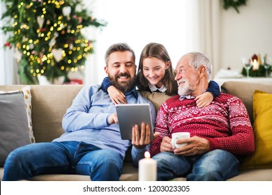 Small girl and her father and grandfather sitting on a sofa at Christmas, using tablet.