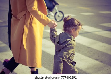 Small girl holding mother's hand on zebra crossing. Unrecognizable mother guiding her daughter while walking a cross the street.