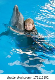 The small girl hugs a dolphin at the dolphin therapy session