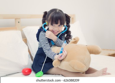 Small girl inject the Teddy Bear by doctor toy set on the bed in bedroom, Kid, occupation, future, job and health care concept