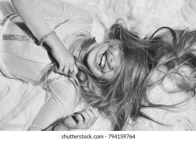 small girl kid with long blonde hair and pretty smiling happy face in prom dress lying on white fabric, closeup
