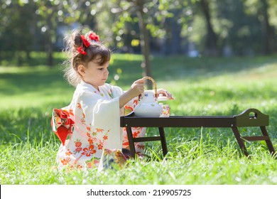 the small girl in kimono sitting on the grass beside the tea table