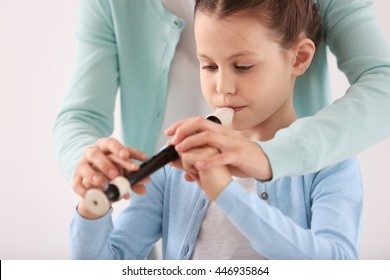 Small girl learning play flute with teacher