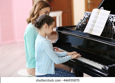 Small girl learning play piano with teacher