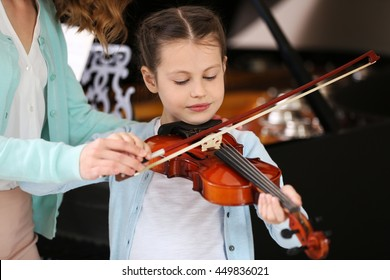 Small girl learning play violin with teacher
