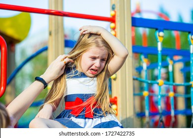 a small girl with long blond hair and blue eyes is hit holding her head and crying. my mother's hand tries to stroke it
