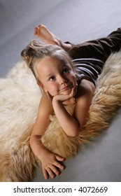 Small girl lying on a fur in studio on gray background.