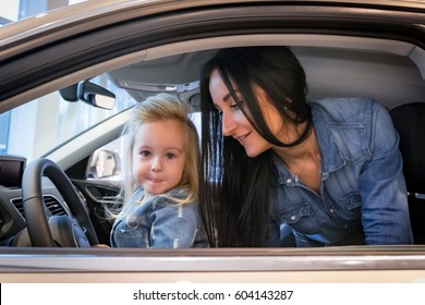 Small girl and mom in exhibition hall for car