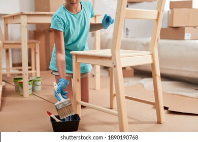 Small girl painting and assembling furniture in new apartment, moving in and being hardworking.