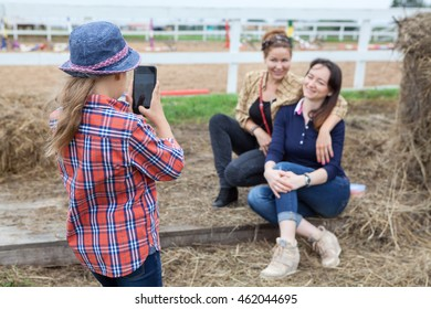 Small girl photographing of two women sitting next to the hay on cellphone