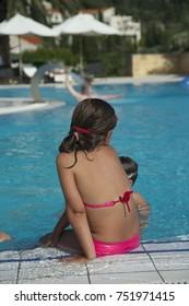 Small girl in a pink bikini seat near the pool, Summer