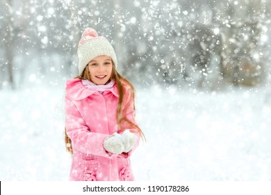 Small girl in a pink jacket playing with the snow outside on holidays