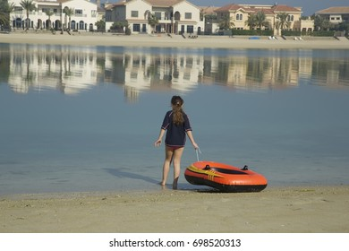 Small girl play with inflatable boat near sea water, Amazing sea background. Palm