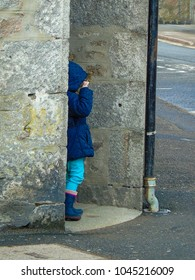 A small girl playing hide and seek, hiding around the corner.