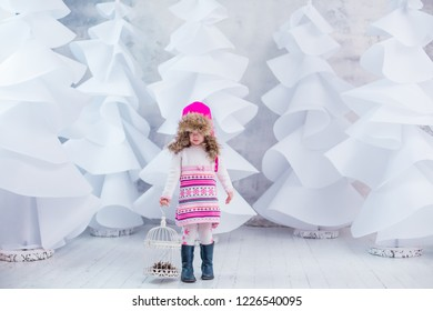 small girl playing on white christmas trees forest background