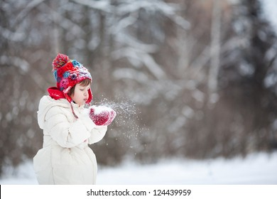 Small girl playing with snow