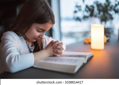 A small girl praying at home.