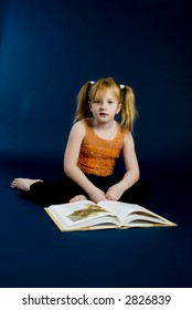 Small girl is reading a book
