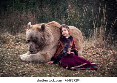 A small girl in the russian traditional costume walking with a real big brown bear in the forest. Late autumn period