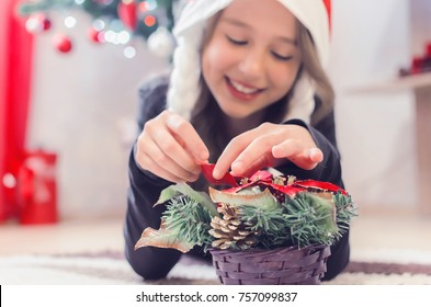 Small girl shows a felt Christmas tree decor. Small girl holds a Christmas tree decor in his hands. Homemade decoration idea for kids. Craft tools and materials on a wooden floor Closeup