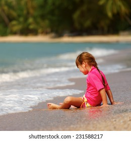 Small girl sitting on sand at beach