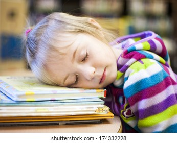 Small girl sleeping on a desk in a classroom