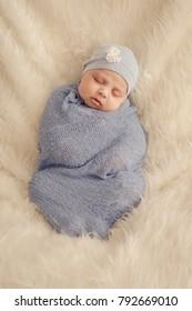 Small girl sleeping and wrapped on fur rug