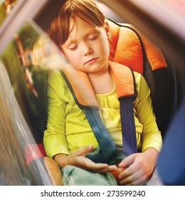 a small girl sleeps in car